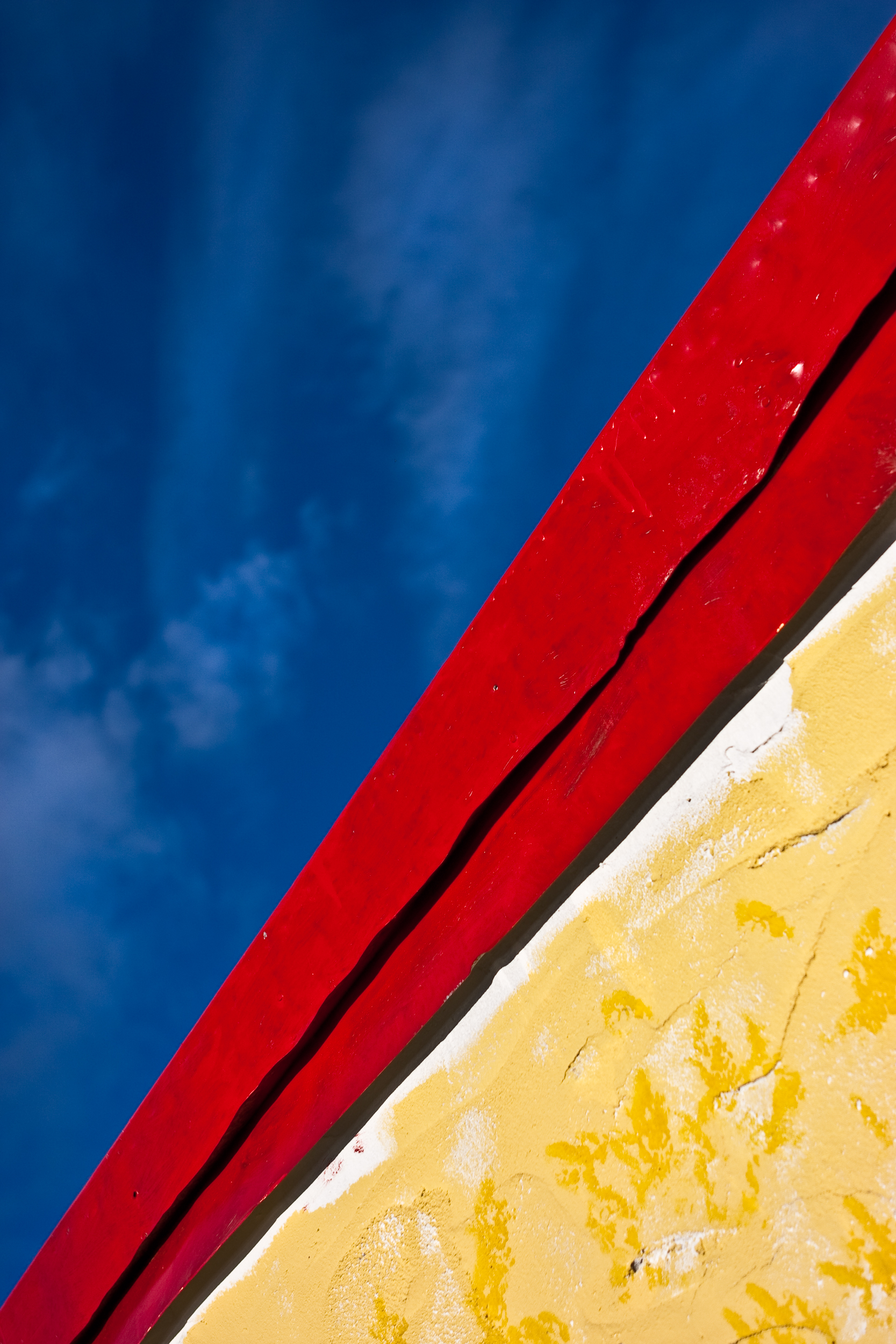 Detail abstract image of a red roof with yellow walls against a cloudy blue sky.