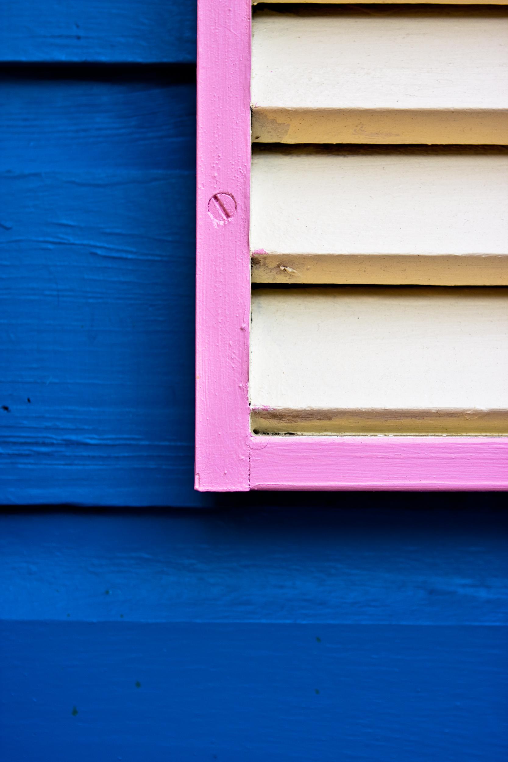 Detail image of pink trim set against blue wood siding.