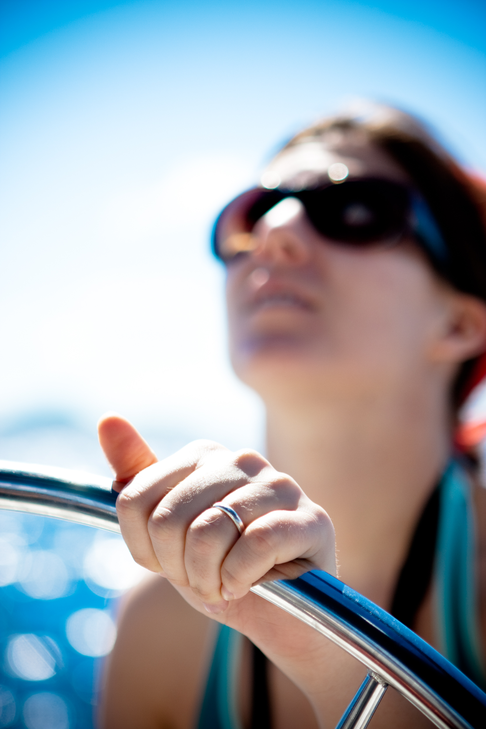 Detail of the hand of a female captain as she guides a sailboat from the helm.