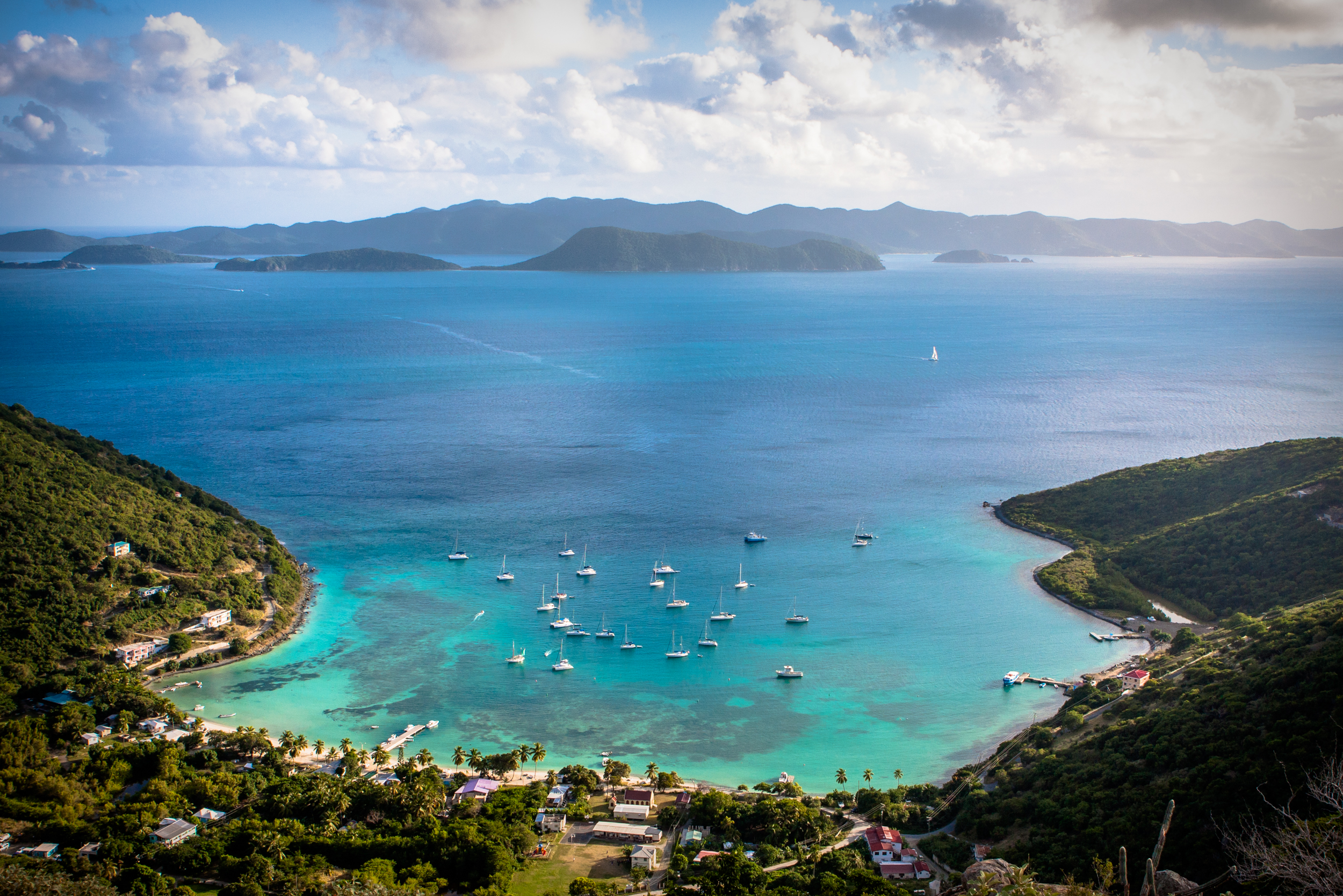 Aerial view of Great Harbor on Jost Van Dyke with sailboats, islands and clear Caribbean water.