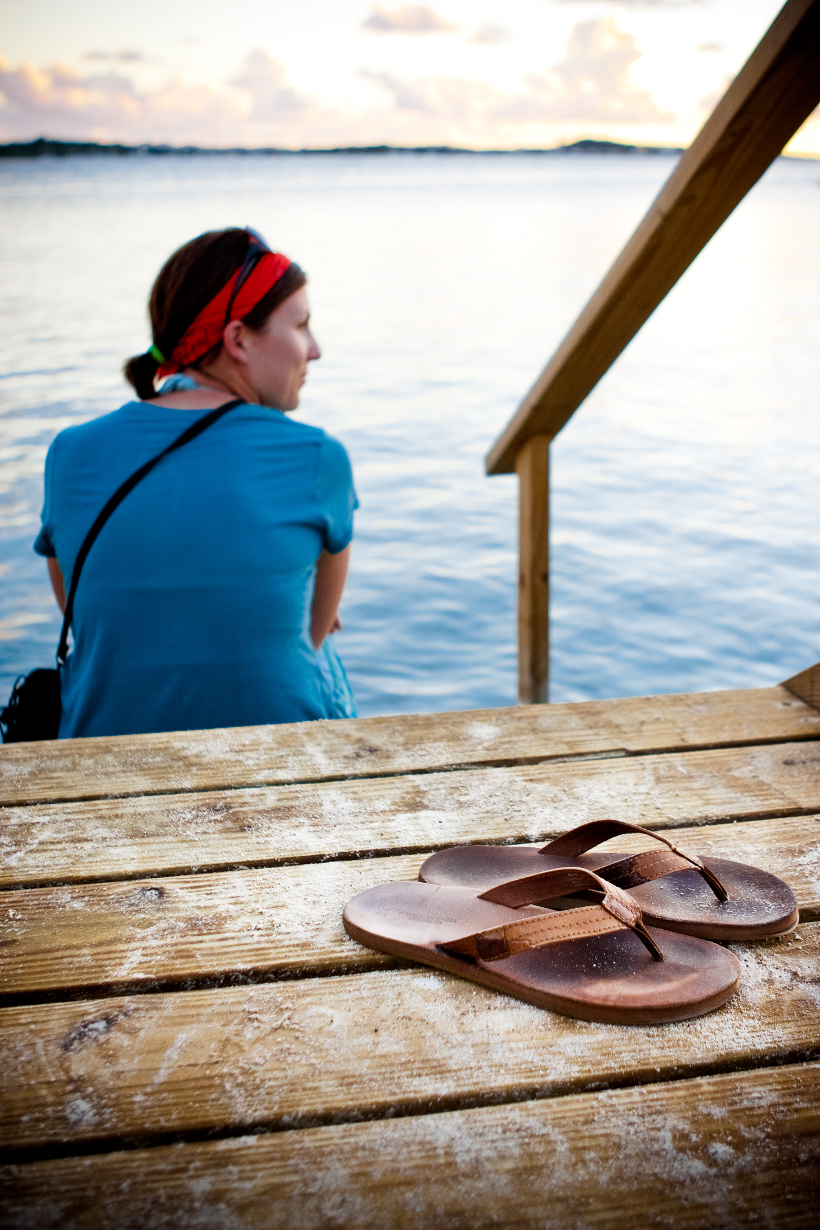 Woman admires a sunset view over blue water during a sailing vacation with her flip flops in the foreground.