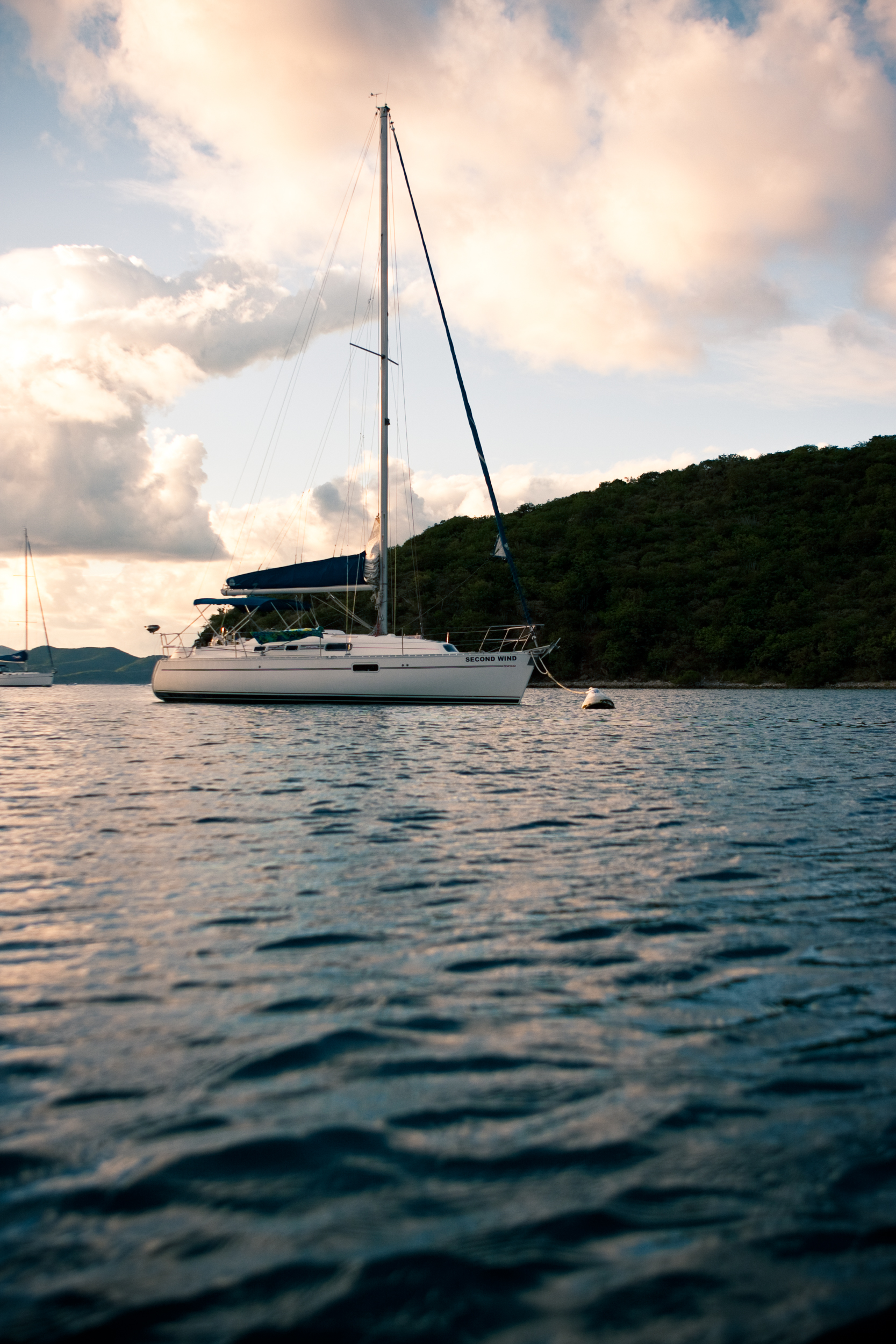 Low angle view of an anchored sailboat as the sunsets behind Caribbean Islands.