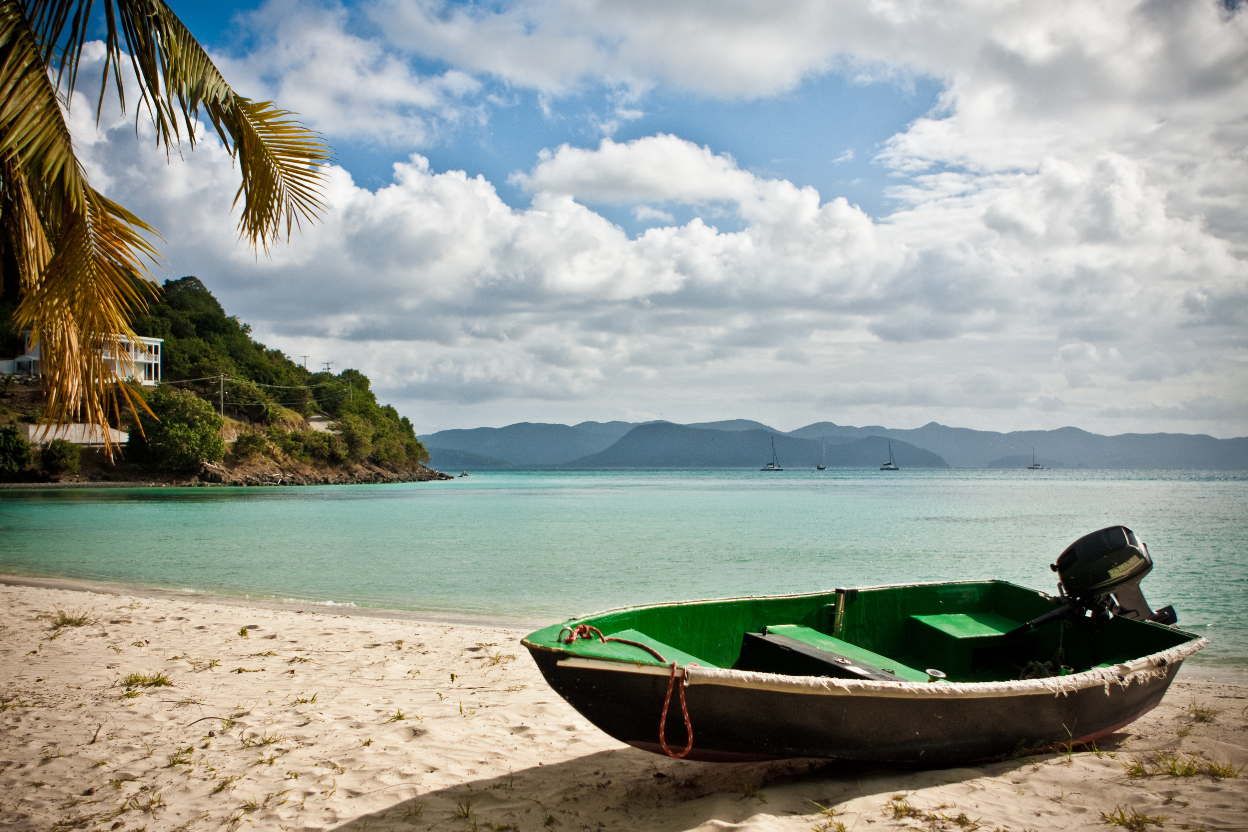 Green dinghy rests on the beach with palm trees, clear water and anchored sailboats in the background.