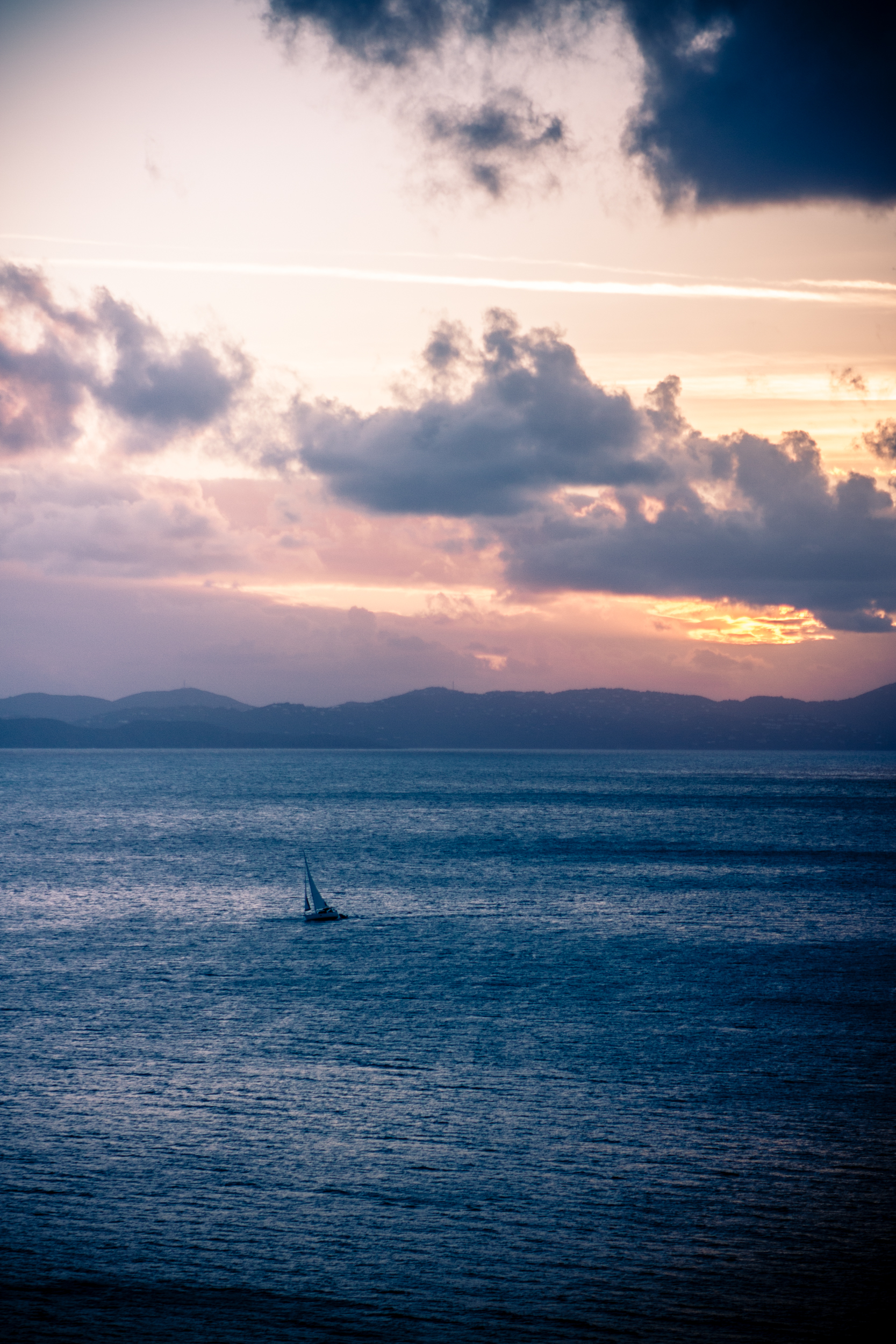 A sailboat crosses the ocean with a beautiful sunset and Caribbean islands in the background.