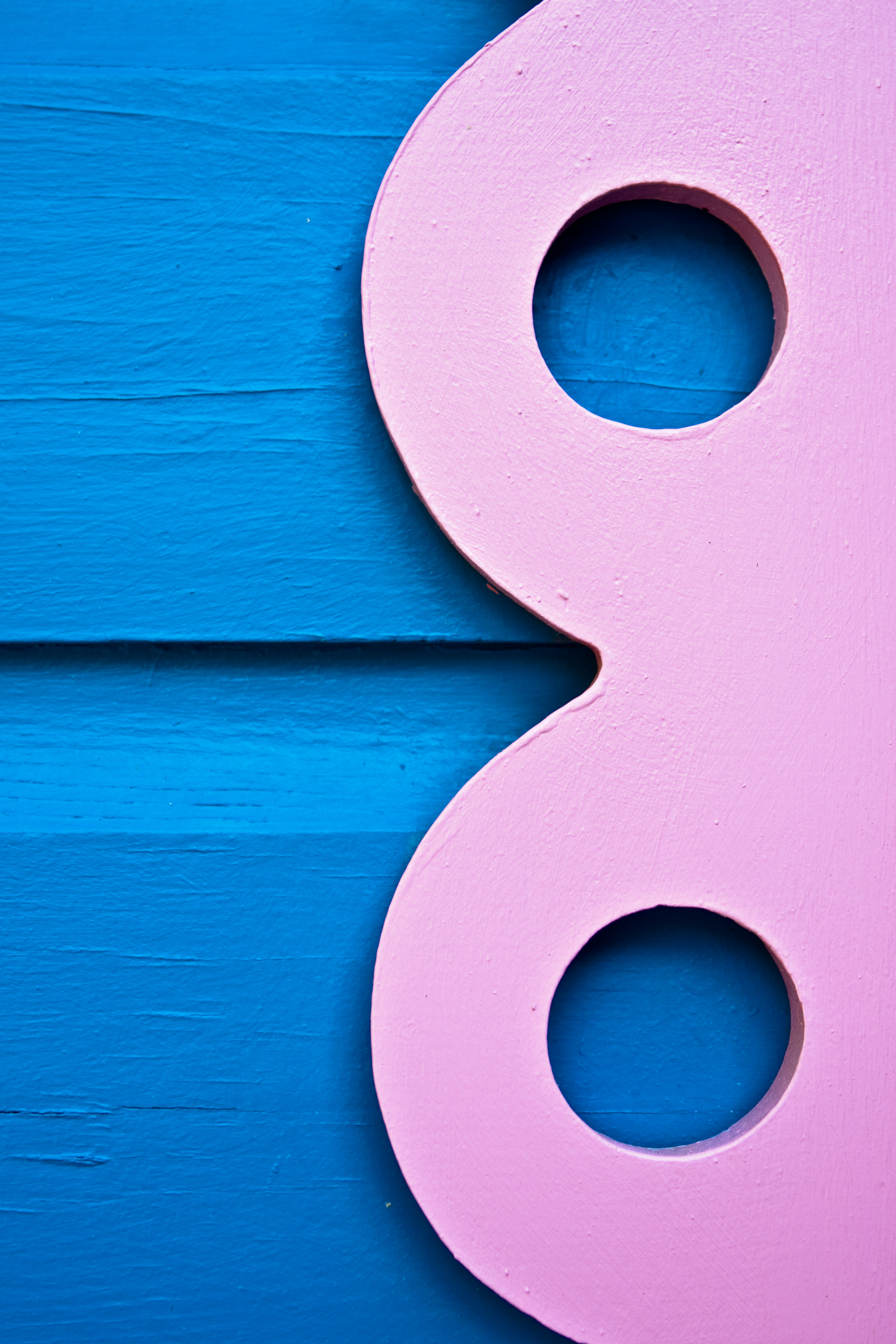 Wood details from a Caribbean house with pink circles and a blue background.