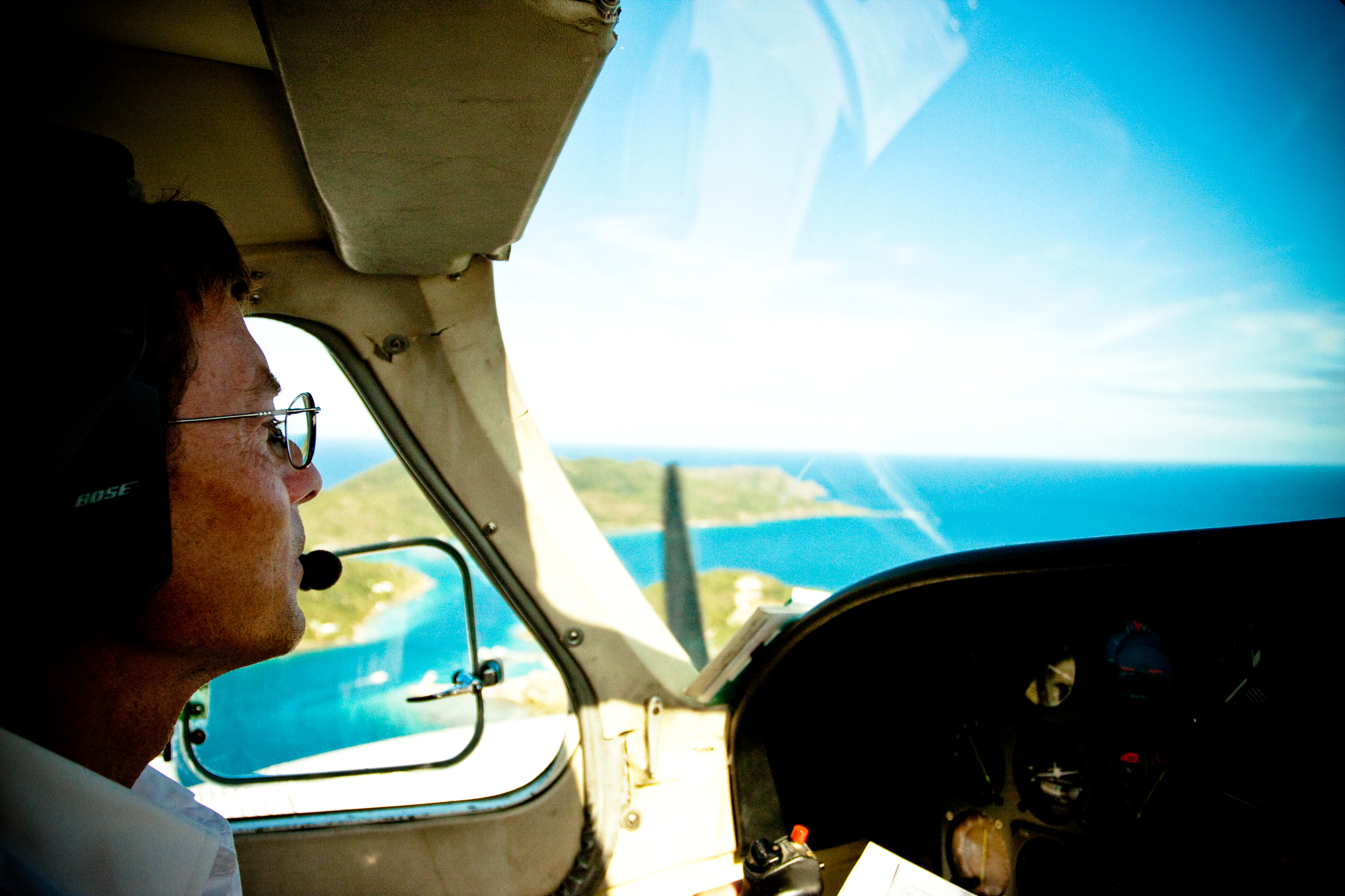 Pilot looks out across blue Caribbean waters during a small inter island flight.