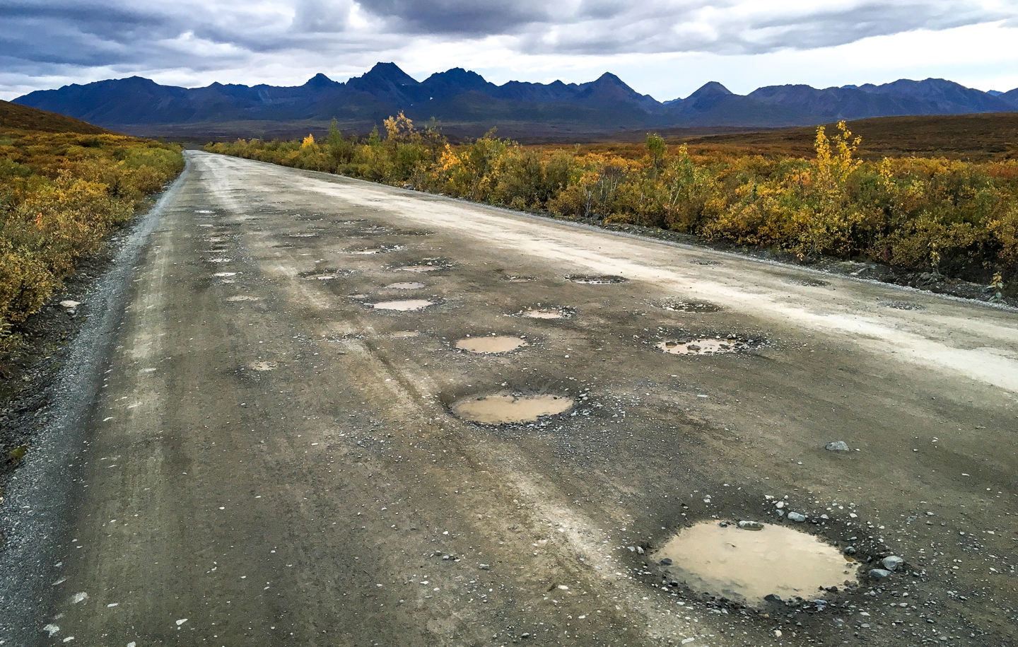 Alcan Potholes - The potholes between Whitehorse and Palmer are intense; it's essentially 662 miles of switchbacks, trees, and potholes that will make you see Jesus. Photo Source.
