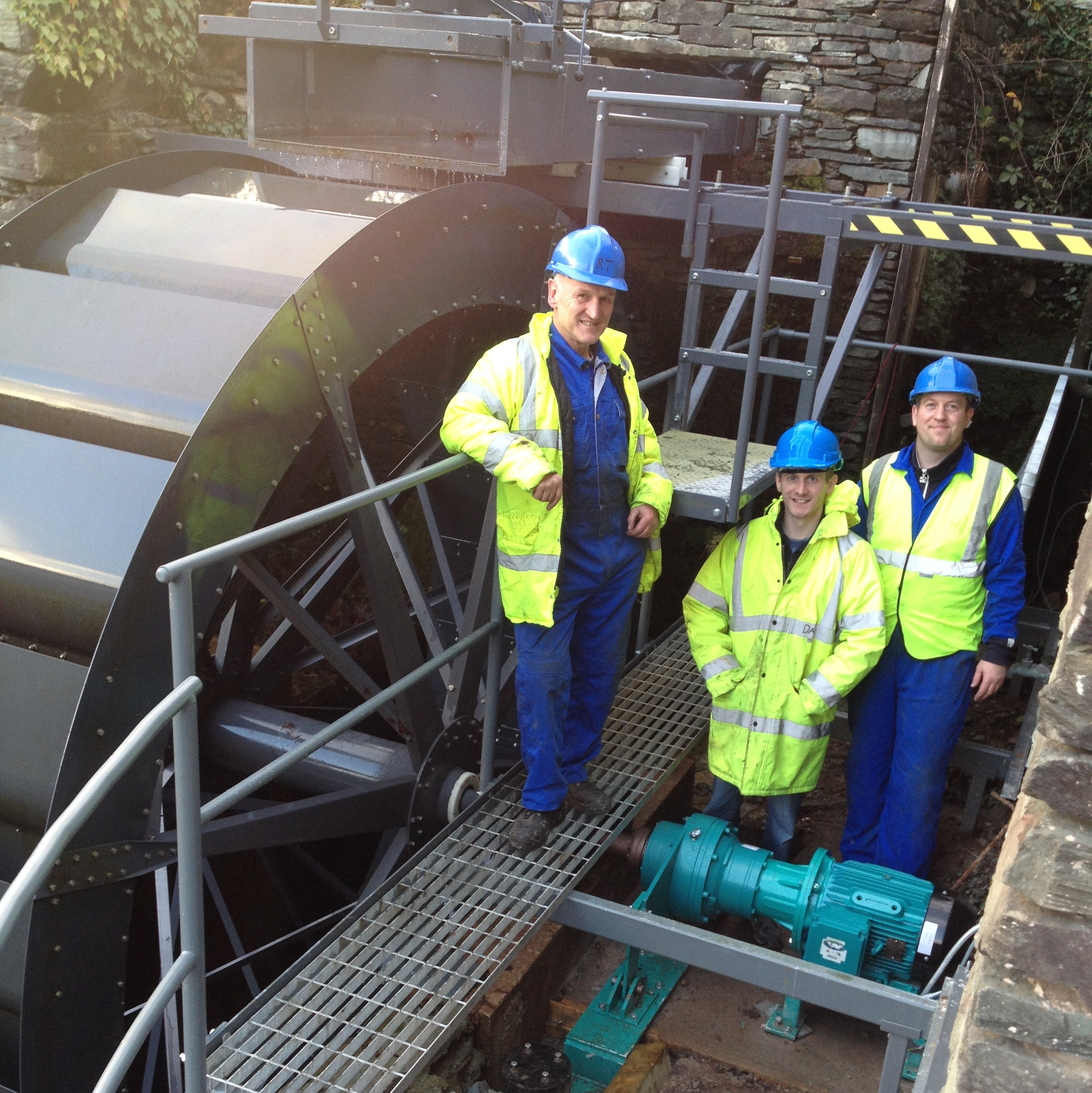 Reg Tiffin (l), Jonathan Smith (c) and David Lightfoot (r) with the waterwheel installed at Langdale