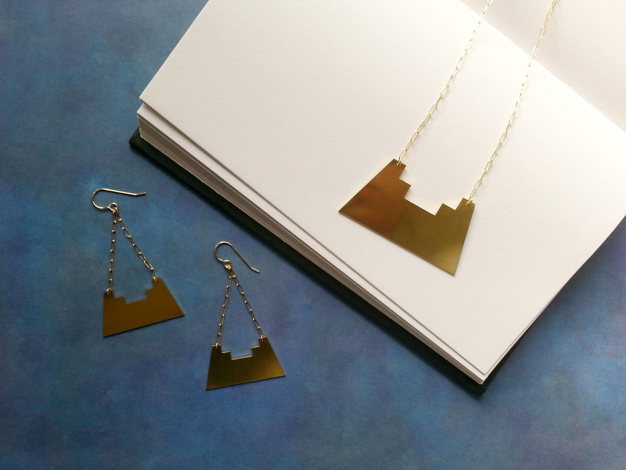 JUARA earrings and necklace. These pieces feature laser cut brass elements and gold-filled chain and findings.