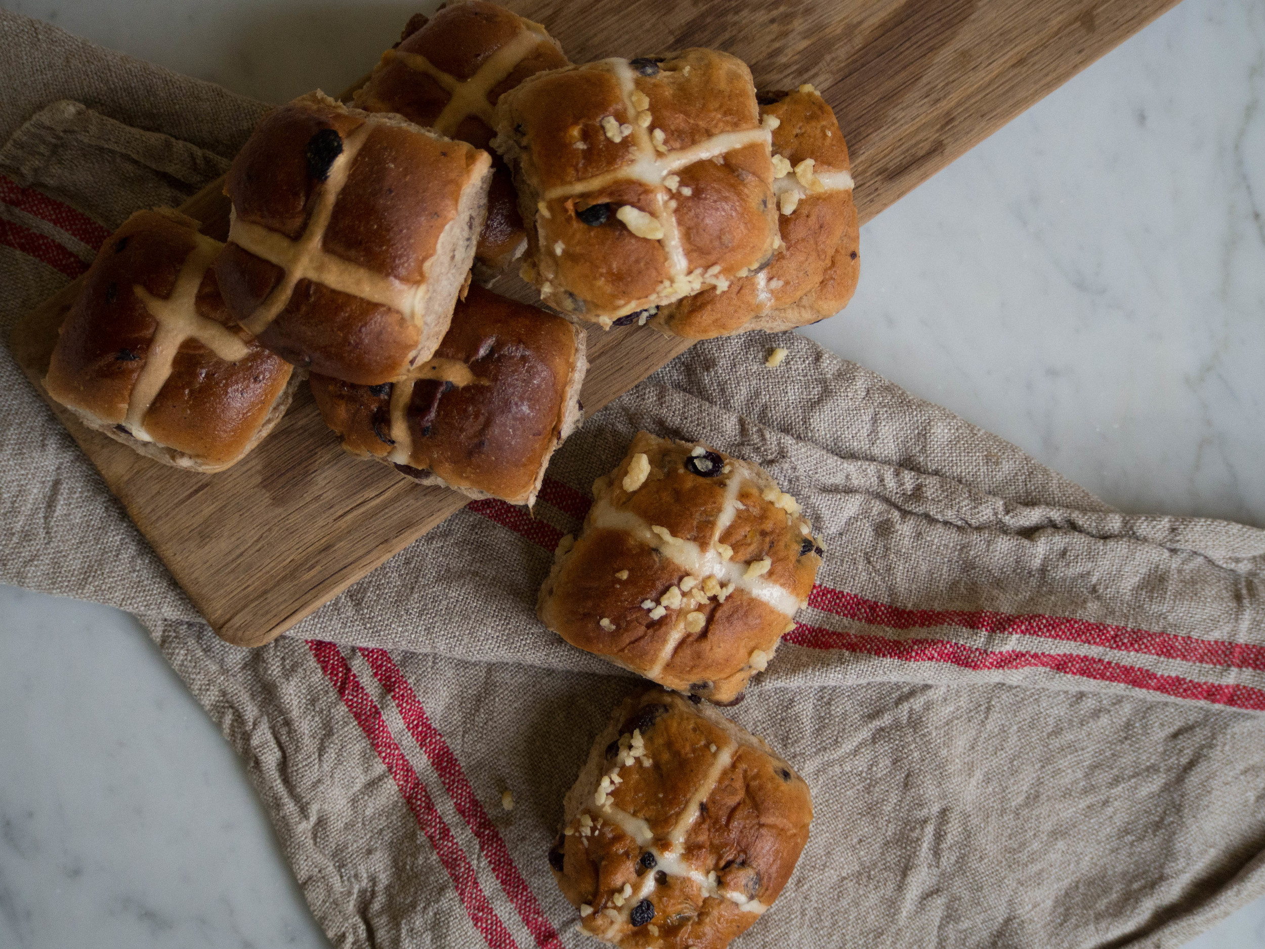 Hot Cross Buns from Baker's Delight (left) and Jamie Oliver's Stem Ginger Hot Cross Buns from Woolworths (right).