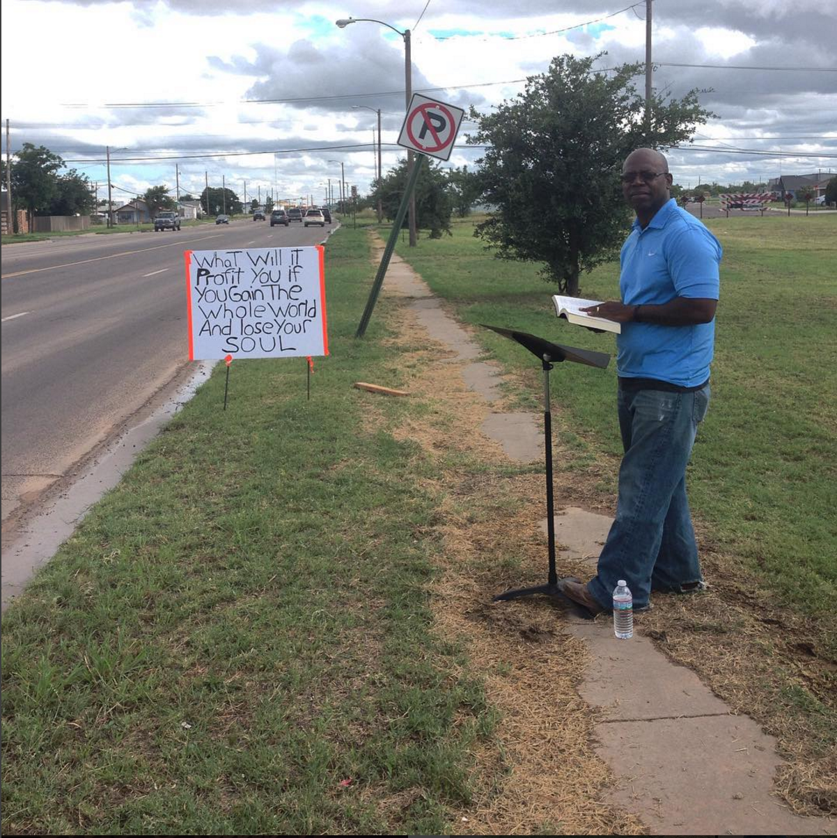 """Midland, TX. August, 2015.  """"What will it profit you if you gain the whole world and lose your soul?"""" Pastor LV Brown reading the psalms. He started the Appostolic Eklesia church after an accident in the oil field that he says should have killed him or at least snapped his back, but he came out of it walking. He had strayed from faith for a little while and this experience prompted him to return to God. So he became a pastor.  #SnapshotLives"""
