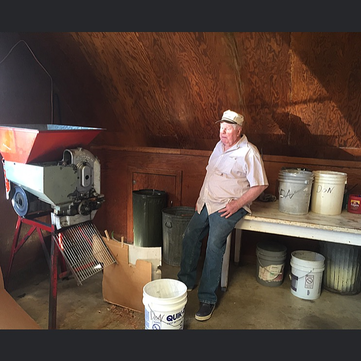 """December, 2015. Midland, TX. Don Edwards, 80, and pecan-cracking machine. I saw a sign on the side of Highway 349 that said """"Edwards Pecan Cracking."""" It stood beside a little house with the blinds drawn and there was a warehouse and a couple trailers in the lot behind it. I decided to stop by and knocked on the door but no one answered. I was walking back to my car when I ran into a small and energetic woman named Shirley Edwards. She said her husband Don could visit with me, he was just then cracking pecans in the warehouse. The whir of the cracking machine grew louder as we approached...  #SnapshotLives    #midlandtx  #pecans"""