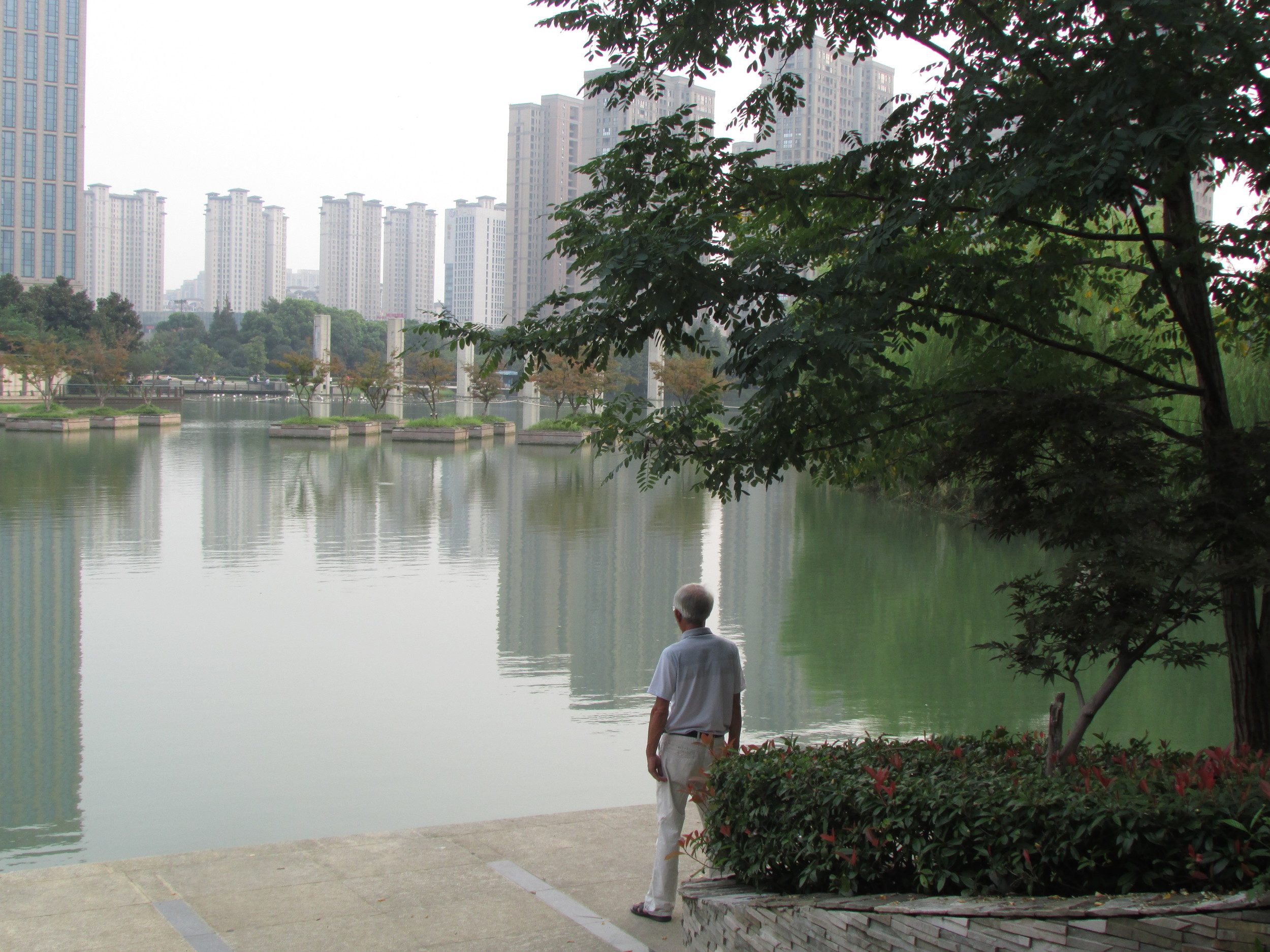 An old man stands in concentration so rigorous that it makes him look sturdier than the skyscrapers.
