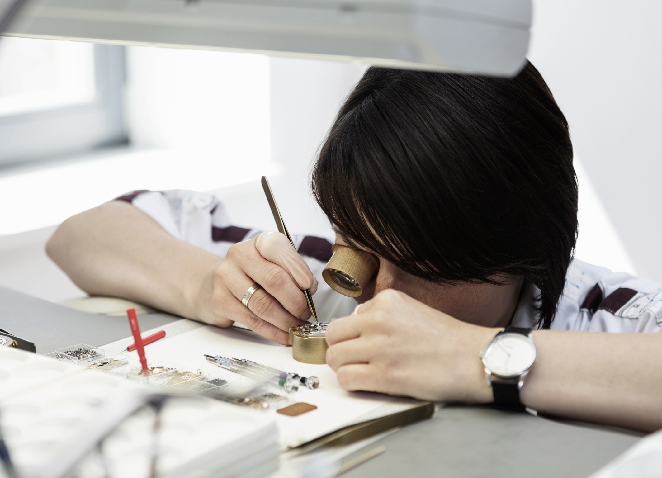 a very patient watchmaker working on a noms caliber. photo courtesy of nomos.