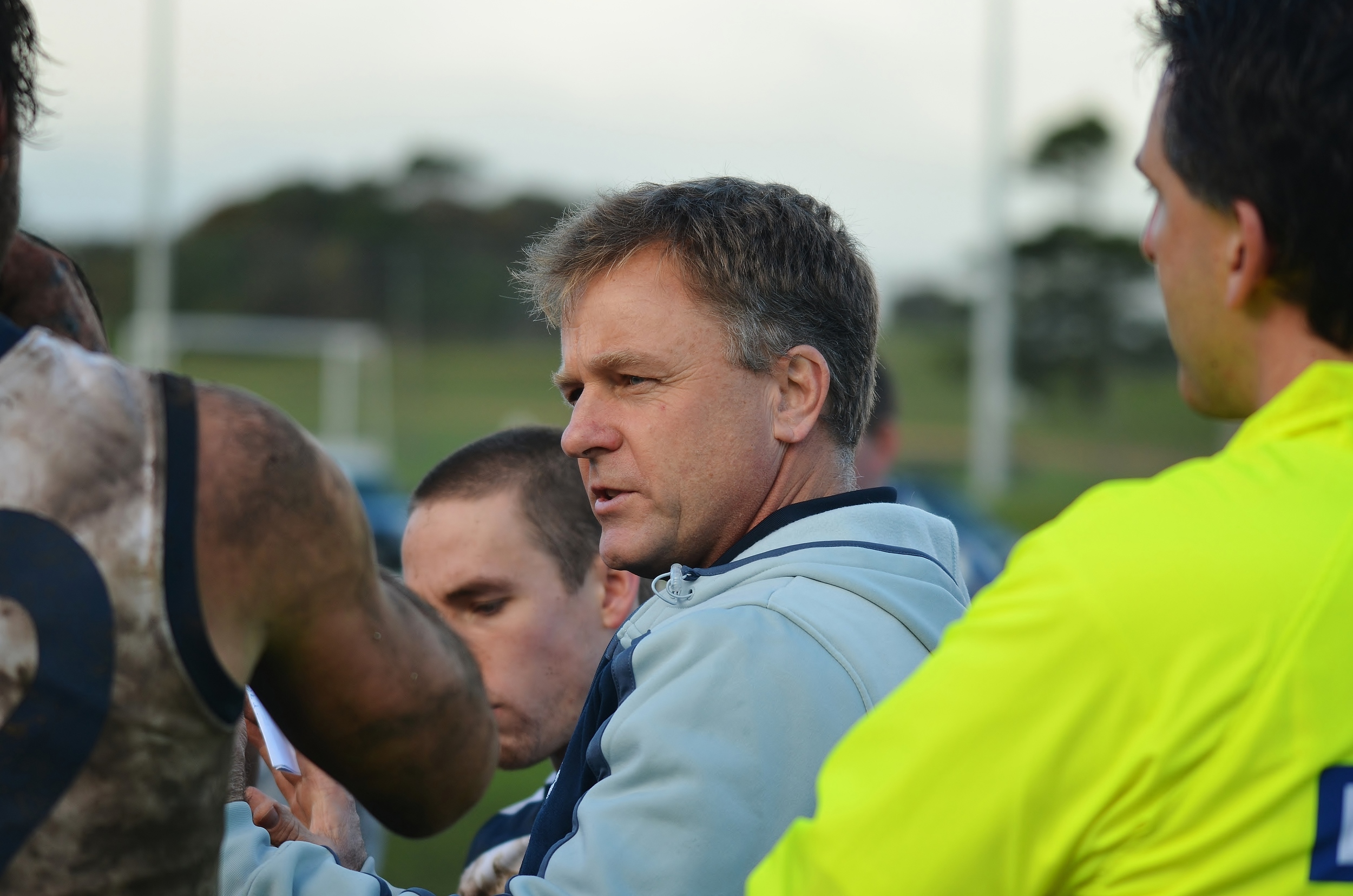 Ron Watt has a word with some muddy players after an intense training session. Watt's approach to coaching has seen the AFLCA reach out to other codesin order to improve Australia's favourite sport. Image supplied by Arj Giese