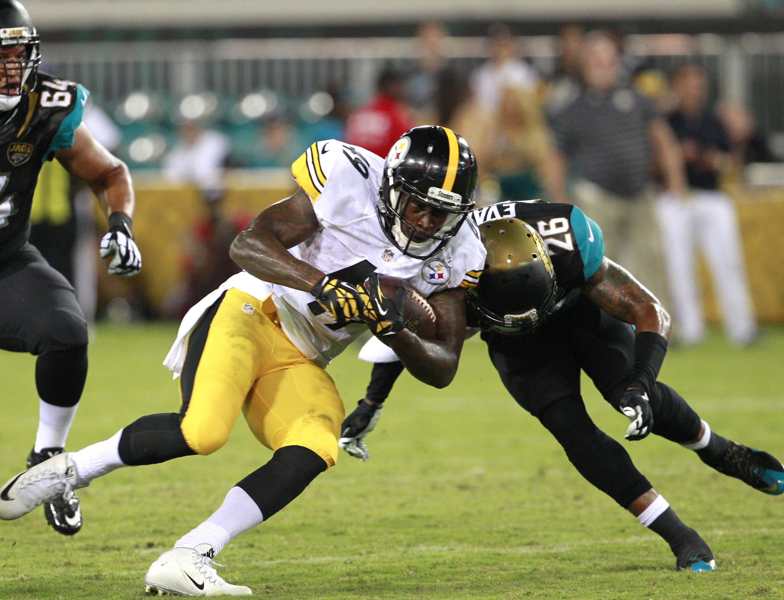 Pittsburgh Steelers running back Jawon Chisholm (49) runs as Jacksonville Jaguars free safety Josh Evans (26) makes a tackle during the second half of a preseason NFL football game. Notice how the tackler is leading with his head. This technique has been directly linked to concussion injuries and is why the NFL is attempting to make the chop tackle technique more prevalent in the sport.  Image supplied by Action Images/Reinhold Matay.