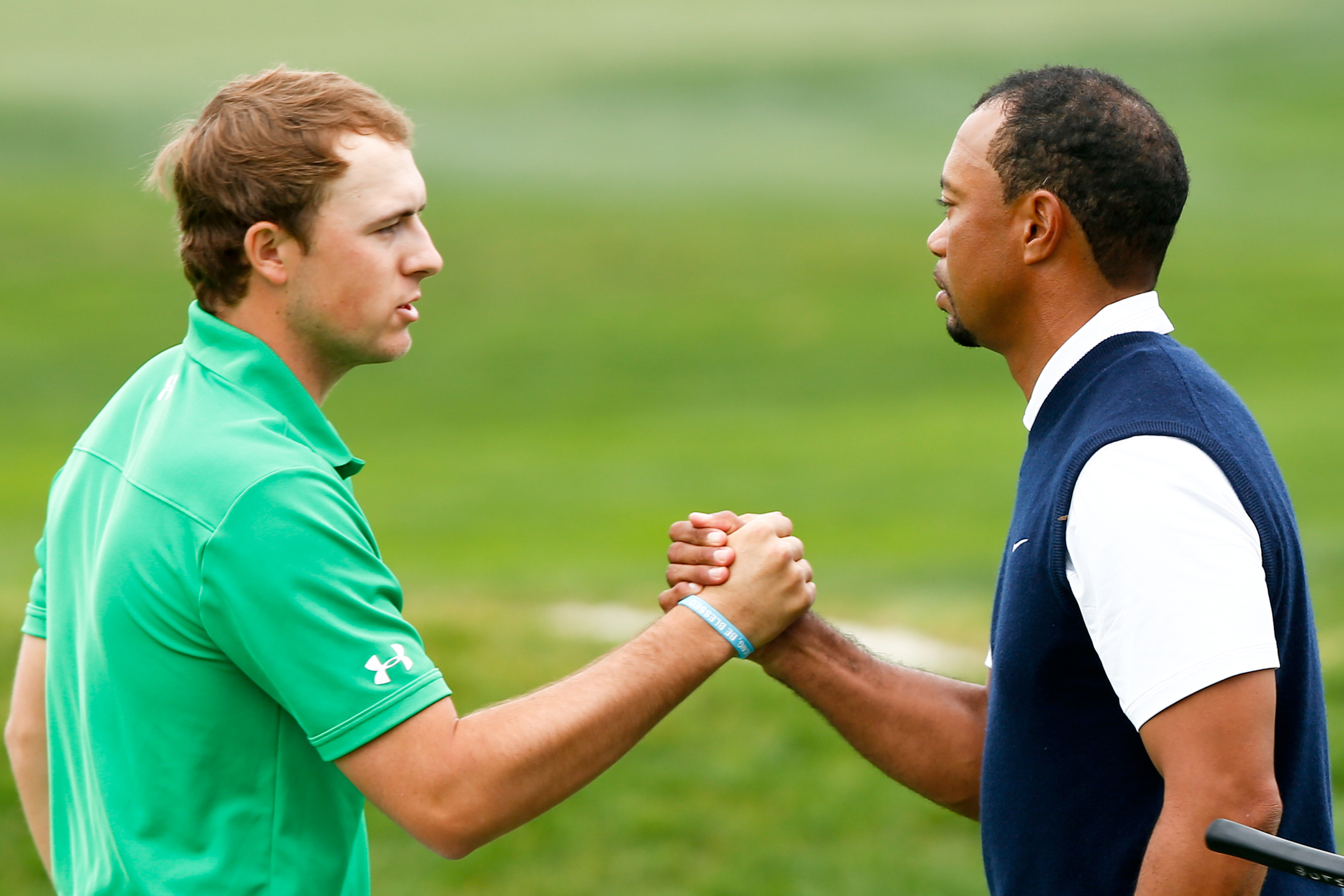 Jordan Spieth (l) shakes hands with Tiger Woods at Farmers Insurance Open golf tournament at Torrey Pines Municipal Golf Course in 2014. Spieth and Woods are two champion golffers who represent contrasting paths to the top.  Image supplied by Action Images / Debby Wong.