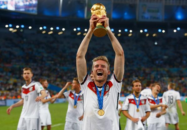 Andre Schurrle celebrates with the FIFA World Cup trophy after Germany defeated Argentina in the 2014 World Cup.