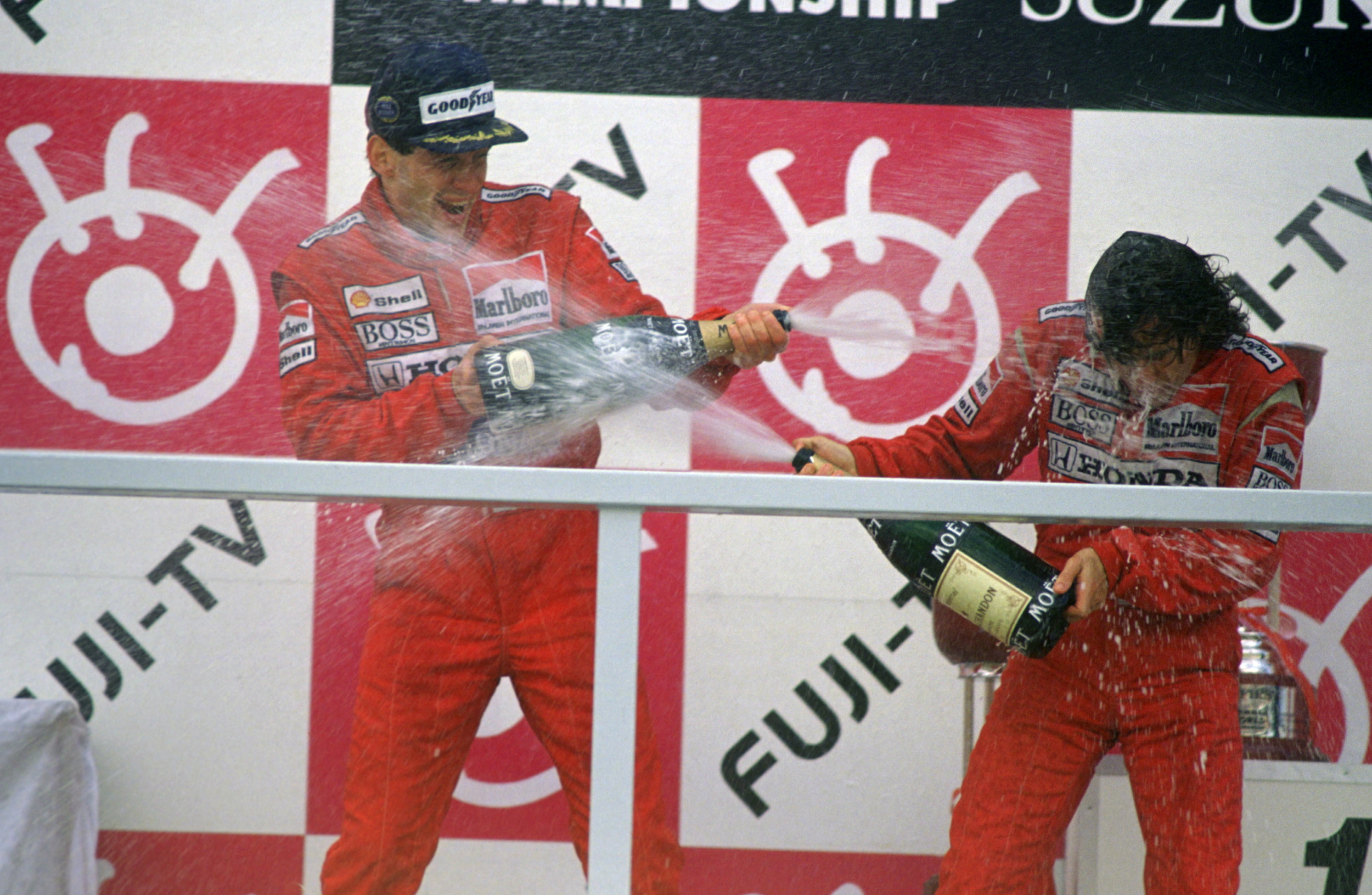 Ayrton Senna (l) celebrates winning the 1988 Formula 1 World Championship, after securing vicory at the Japanese Grand Prix, by spraying his McLaren team mate, Alain Prost (r) with champagne. The two would go on to forge a rivalry that has passed on into F1 folklore. Image supplied by Action Images /Crispin Thruston.