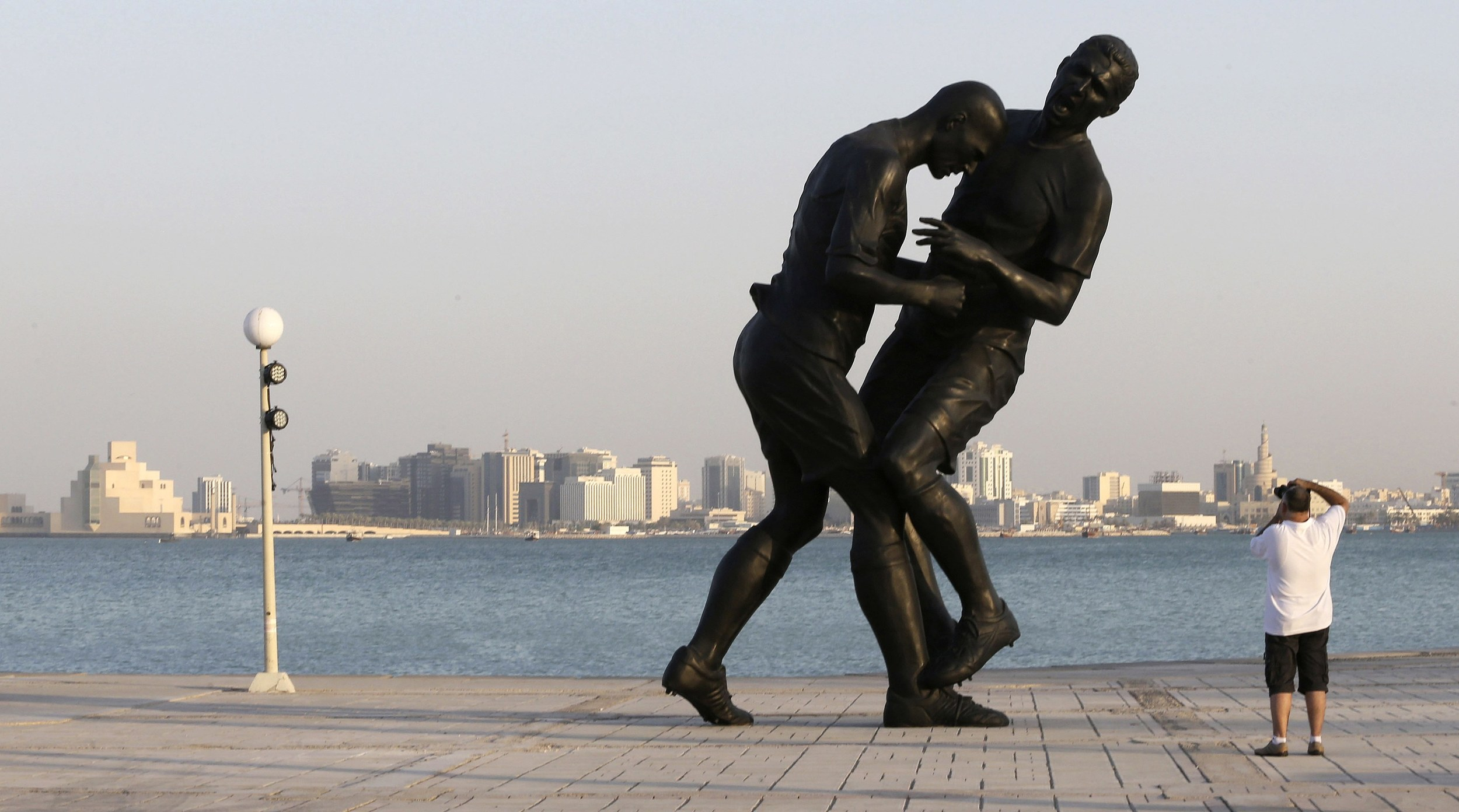 A man takes pictures of a bronze sculpture titled 'Coup de Tete' by Algerian-born French artist Adel Abdessemed during its installation on the Corniche in Doha October 7, 2013. The sculpture, which was bought by the Qatar Museums Authority, was removed on October 28, 2013 after generating criticism from religious conservatives, according to local media. The art work portrays French footballer Zinedine Zidane headbutting Italian player Marco Materazzi during the 2006 World Cup. Image supplied by Action Images