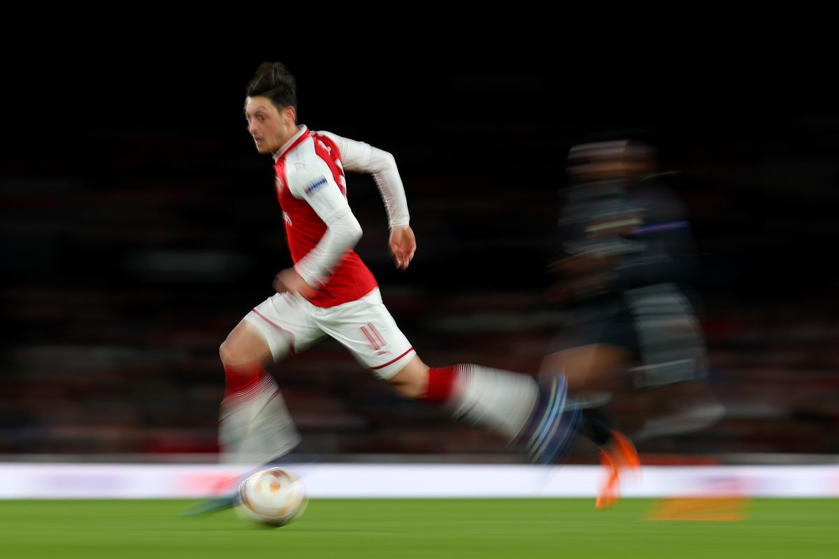 Arsenal's Mesut Ozil ghosts past a CSKA Moscow defender in a Europa League match.