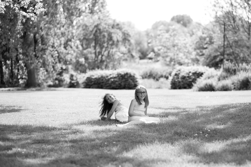 sisters sitting on grass in park