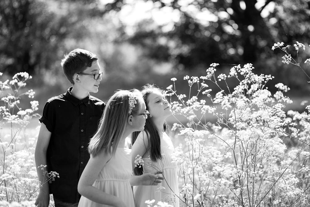 kids smelling flowers in park