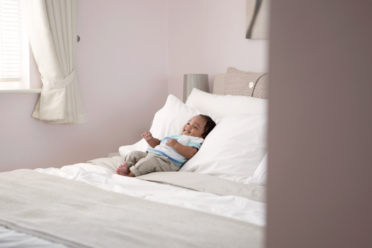 baby smiling on bed - lifestyle photography at home
