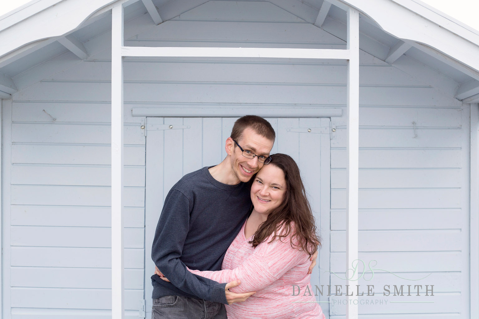 couple in front of blue beach hut - seaside engagement photo shoot