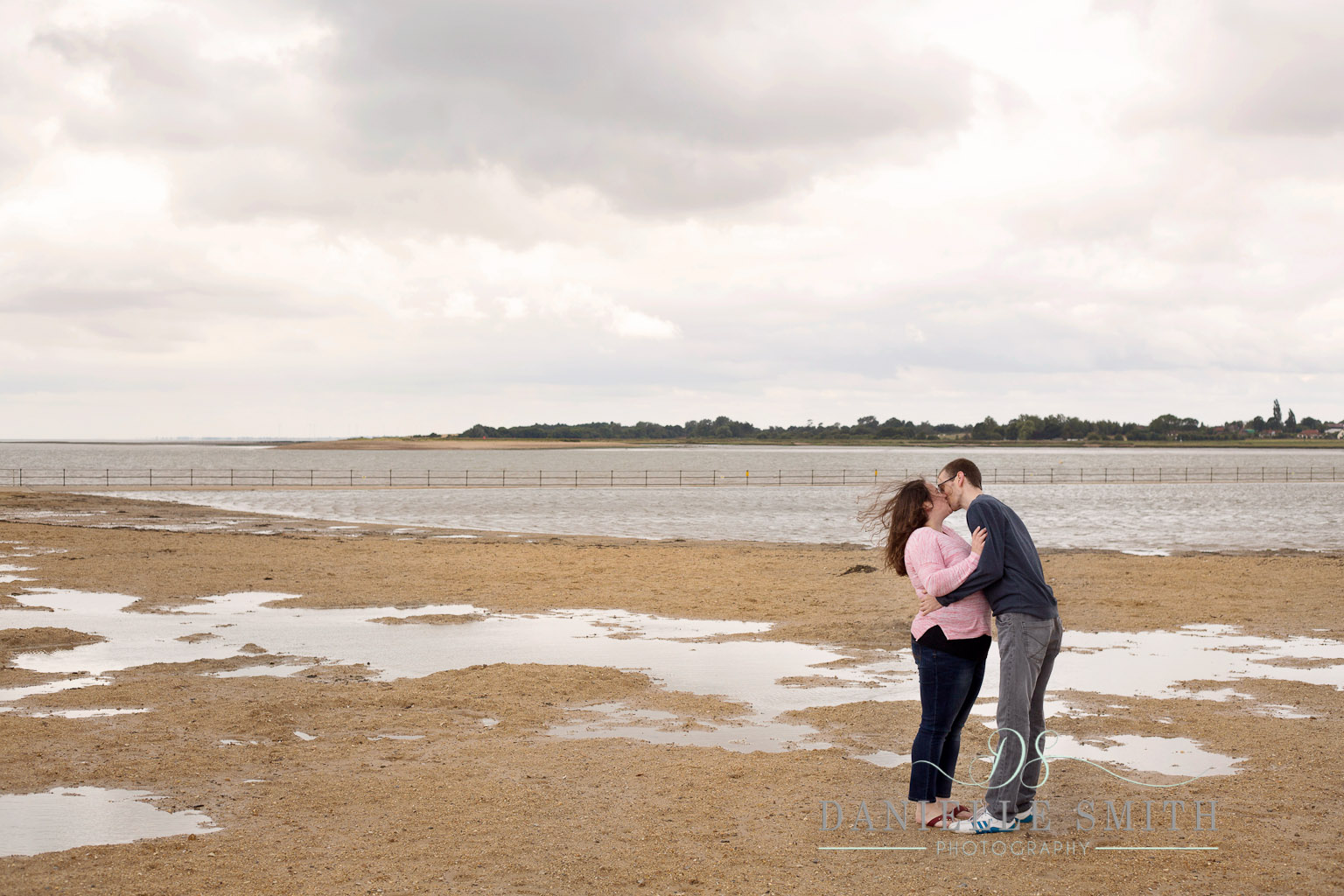 couple kissing on windy day at seaside