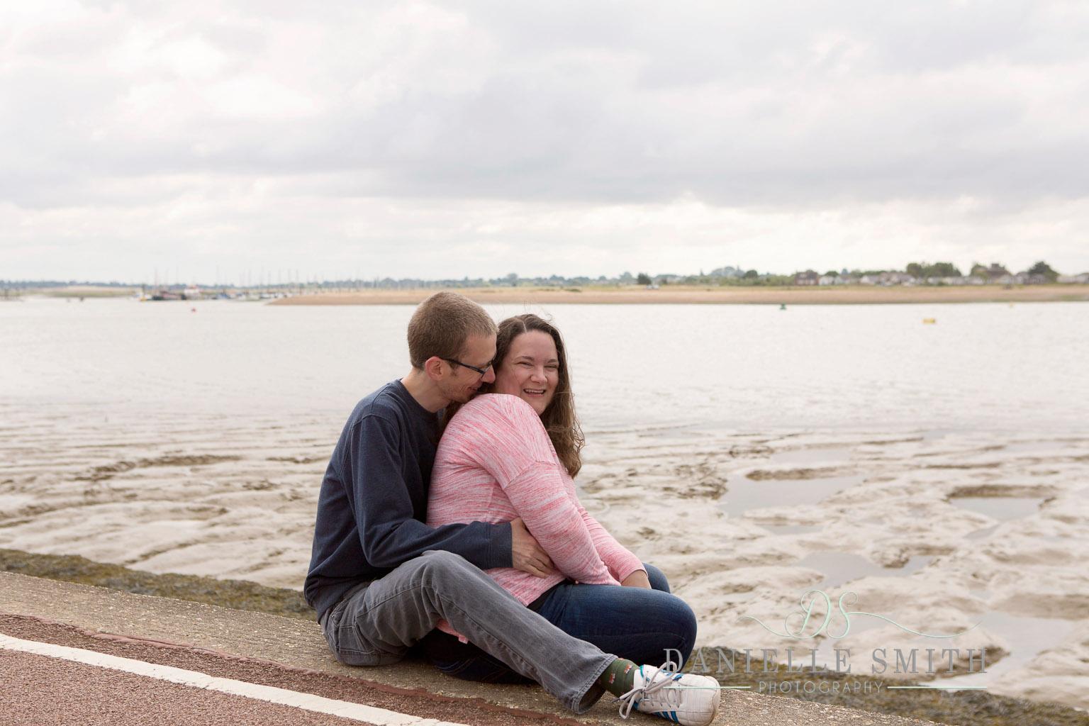 couple hugging by seaside - seaside engagement photo shoot