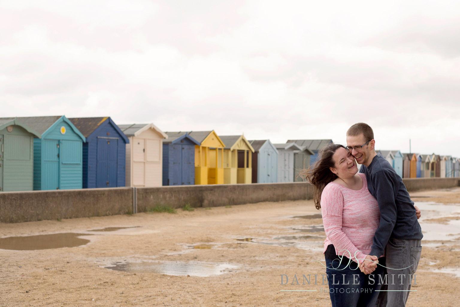 couple laughing on beach - seaside engagement photo shoot