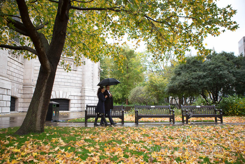 couple walking with umbrella in autumn