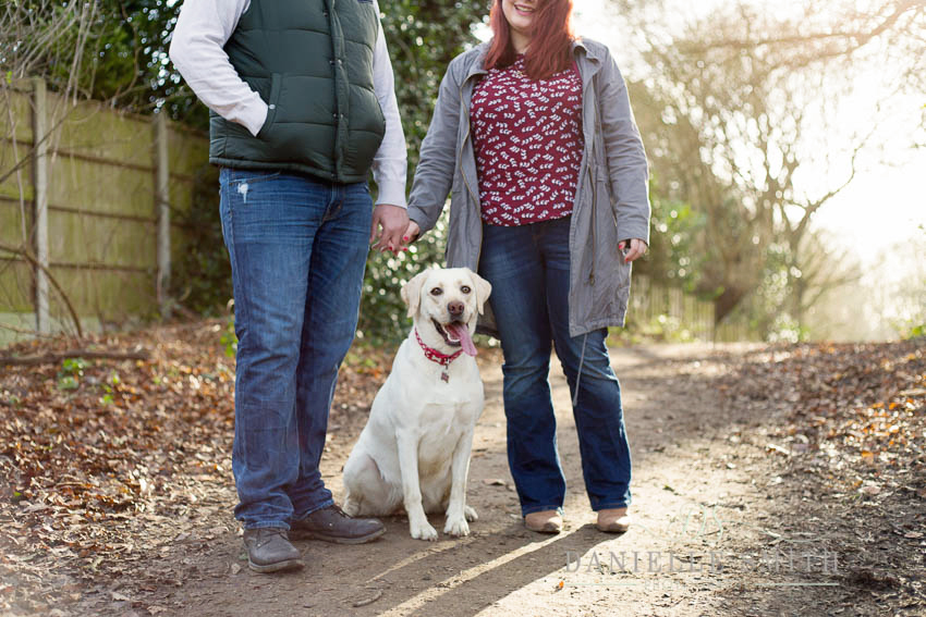 dog sitting between couple in woods