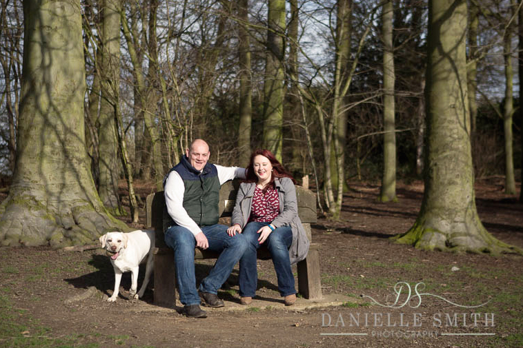 couple with pet dog in woods