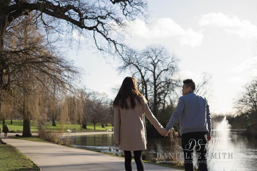 couple walking around lake in park