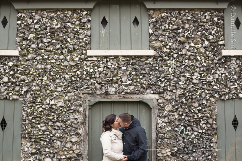 couple kissing in front of stone house