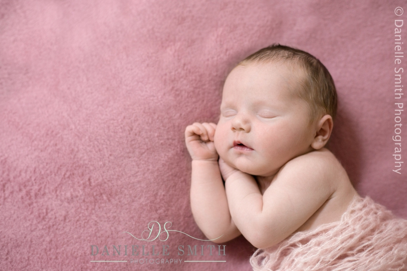 baby girl asleep on pink background