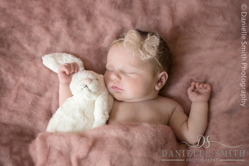 baby girl cuddling rabbit