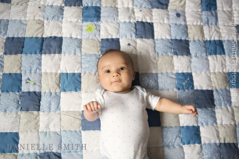 baby boy laying on blue patchwork blanket