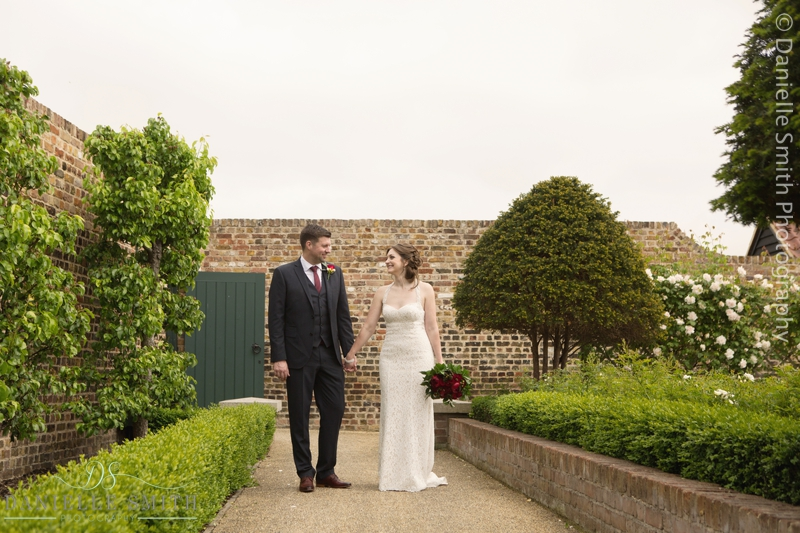 bride and groom walking in walled gardens