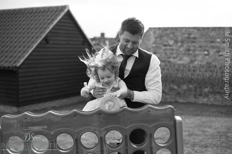 groom lifting little girl up to play connect 4