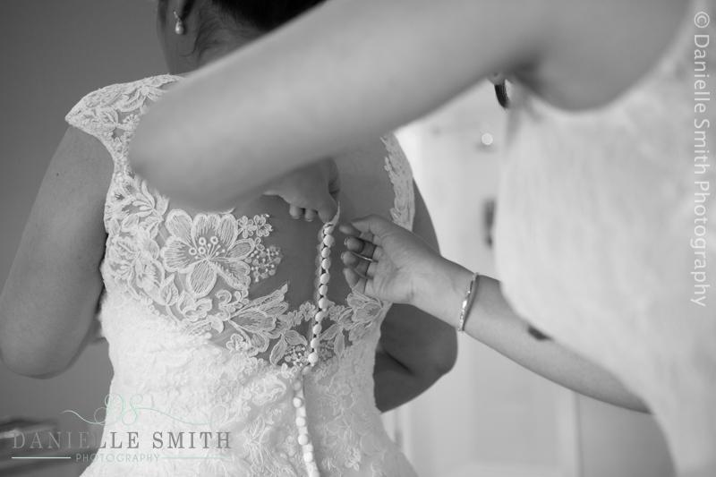 bridesmaid doing back of brides dress up