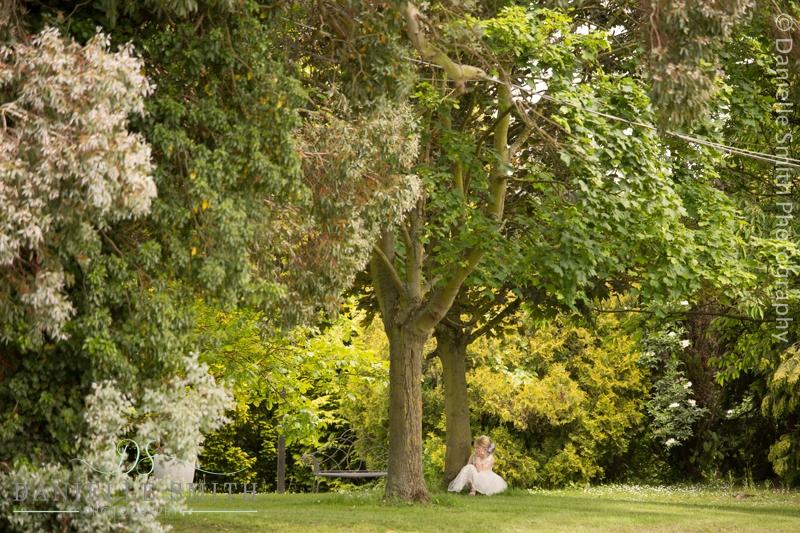 flower girl sitting under tree