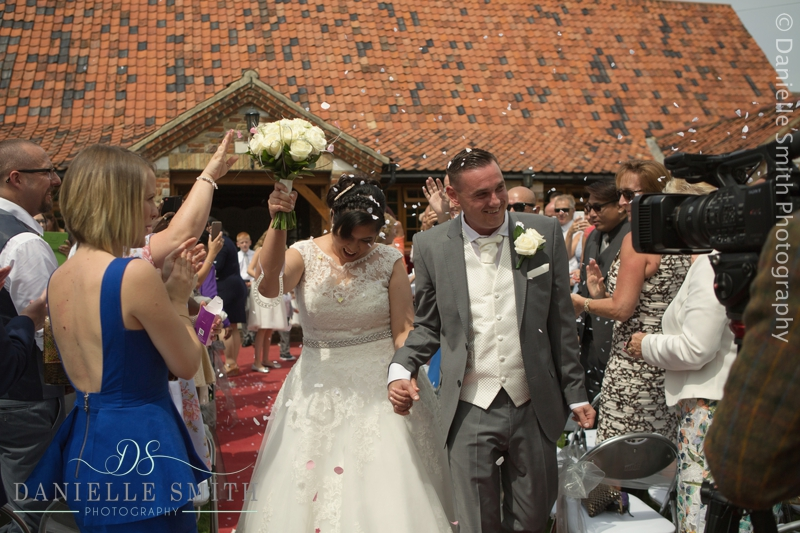 bride and groom walk down aisle with confetti