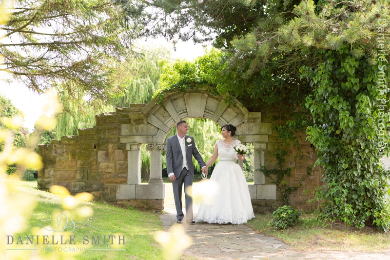 bride and groom walking by arch
