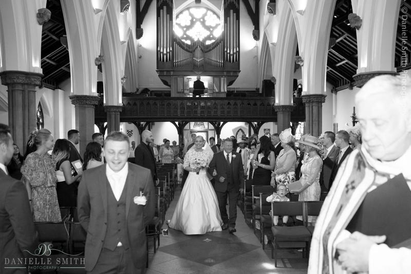 bride and dad walking down church aisle