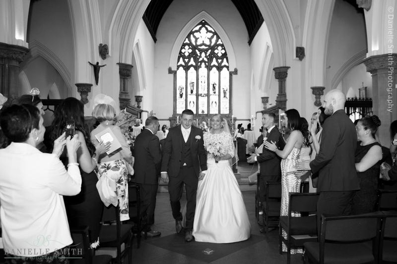 bride and groom walking down church aisle