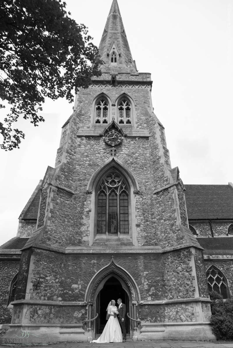 bride and groom outside church tower in Romford