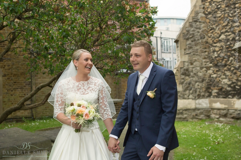 bride and groom laughing outside church